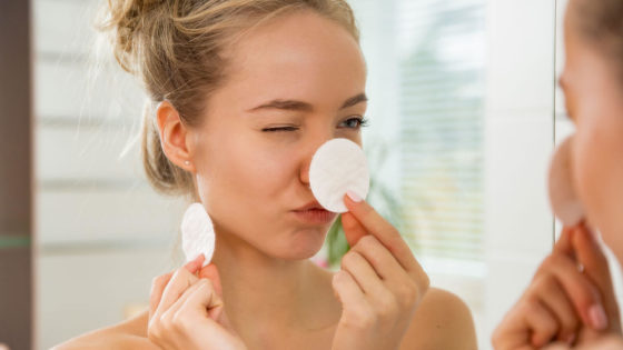 Woman with blond hair is covering her nose with a cotton pad