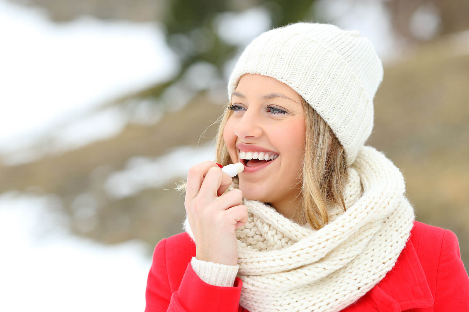 Woman with a white scarf and beanie is putting lip balm on her lips