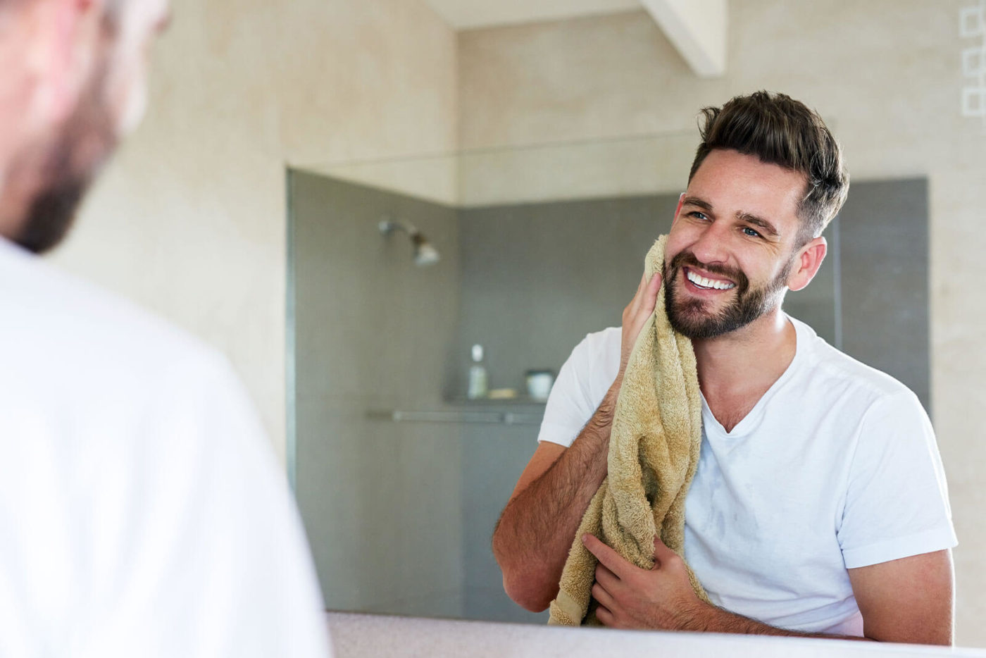 Smiling man with bead is drying his face with a soft towel
