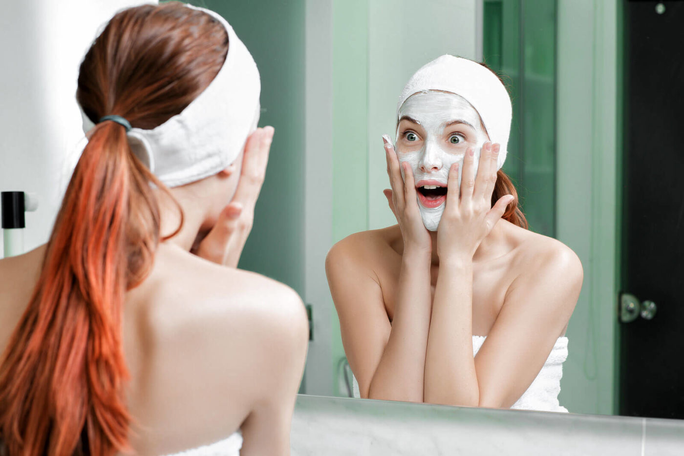 Woman with red hair has covered her face with skin care.