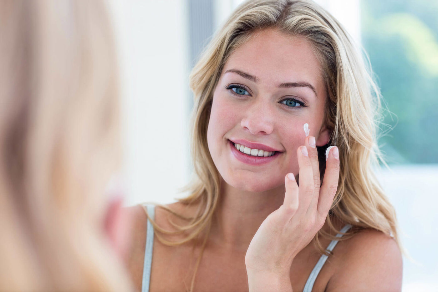 Woman with blond hair is smiling and putting skincare on her cheeks with her fingers